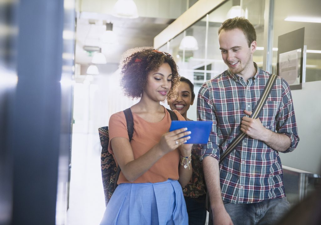 Colegas usando um tablete enquanto conversam andando pelo corredor de uma escola.