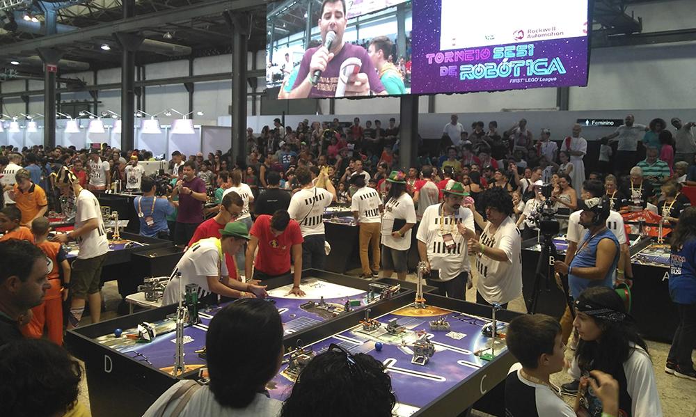 Alunos de diferentes idades reunidos ao redor de uma mesa observando robôs num torneio de robótica.