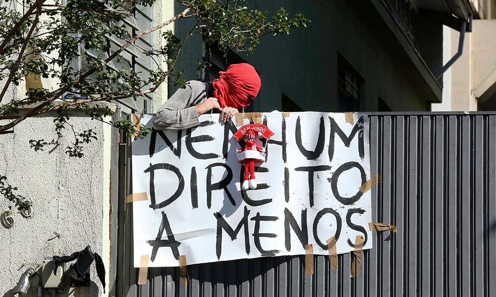 """Ativista com rosto mascarado de vermelho segura a placa escrita """"Nenhum direito a menos"""""""