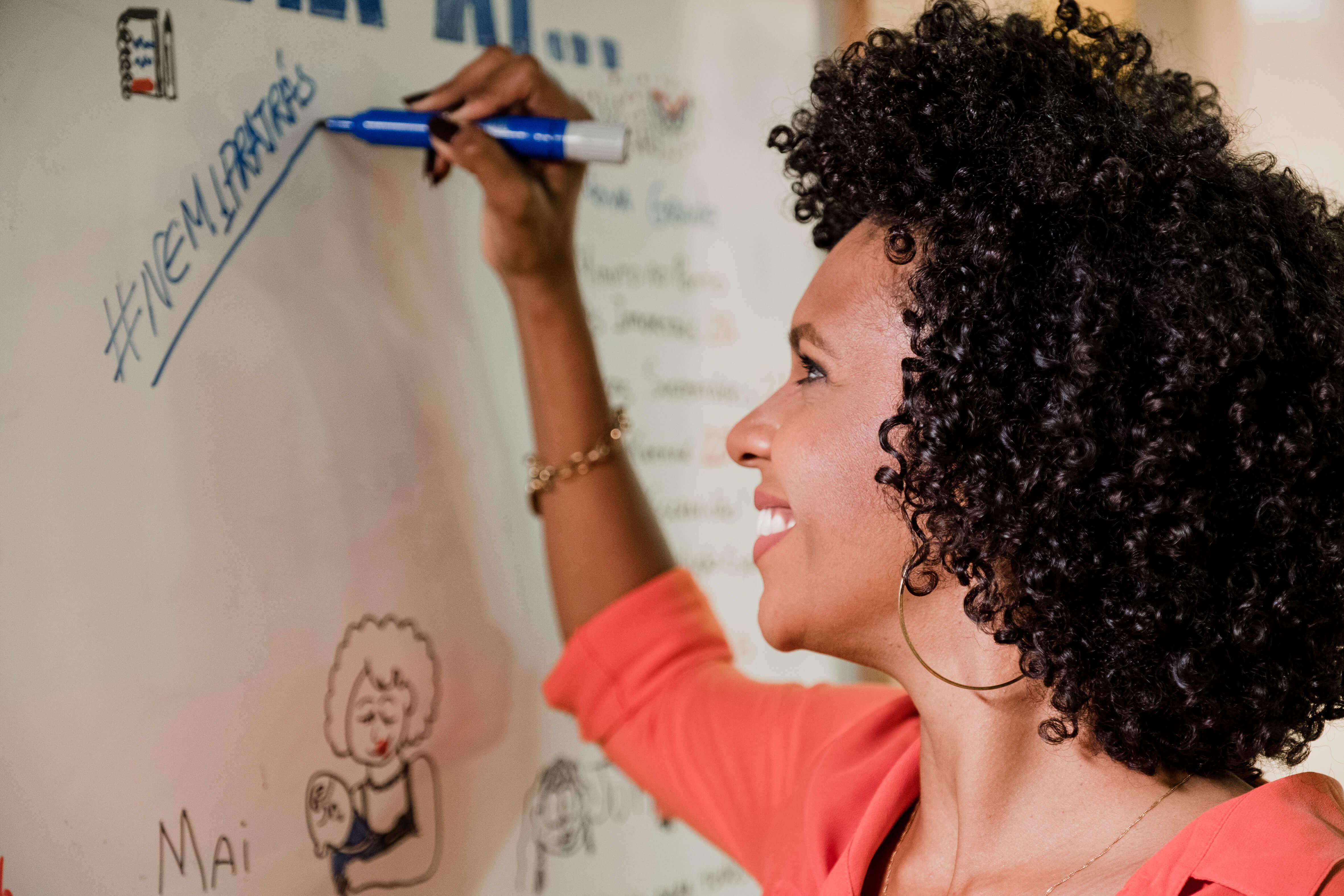 Jornalista negra Luciana Barreto sorri para quadro branco enquanto escreve no Nem1Pratrás