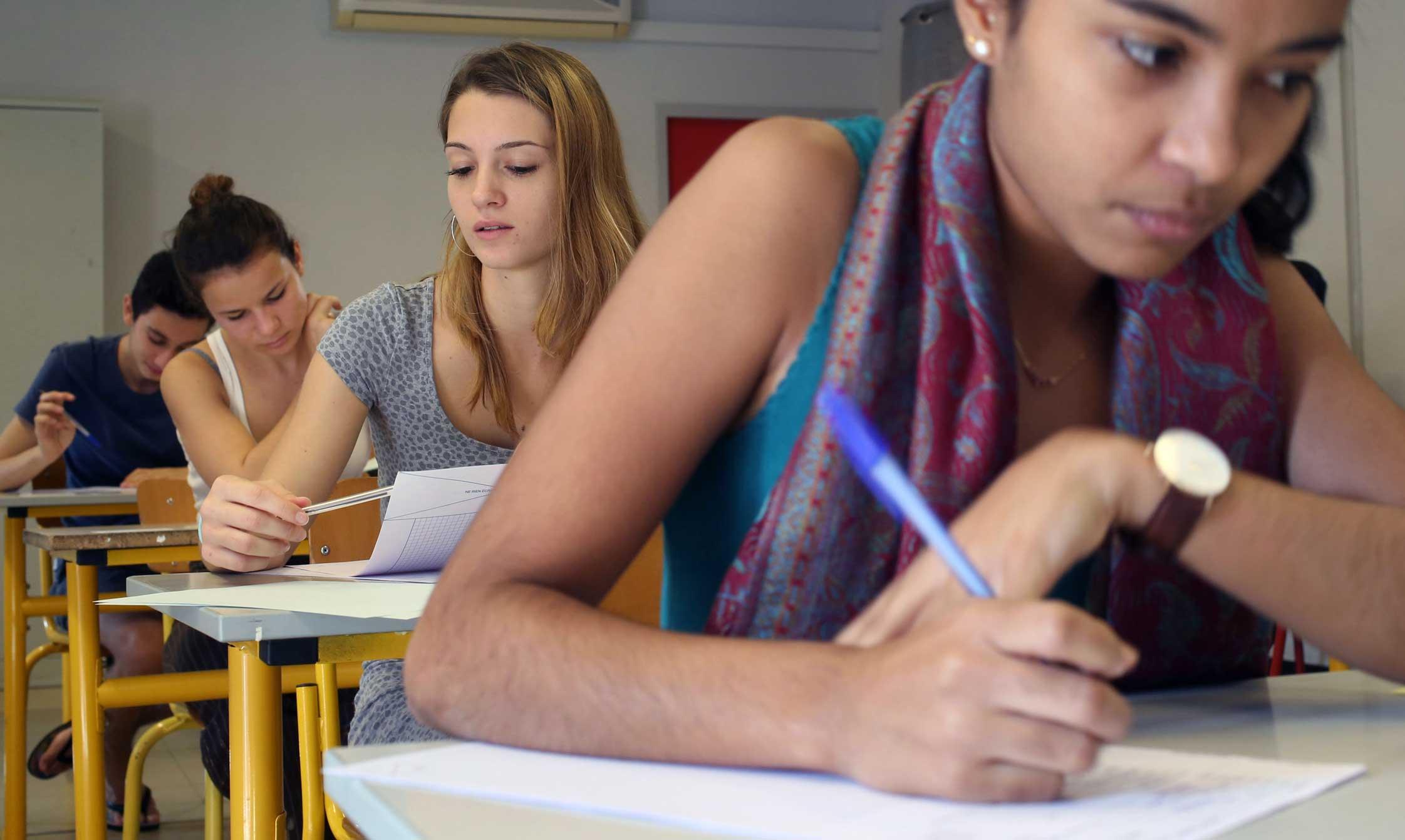 Estudantes sentadas em fileiras escrevendo em um papel dentro da sala de aula