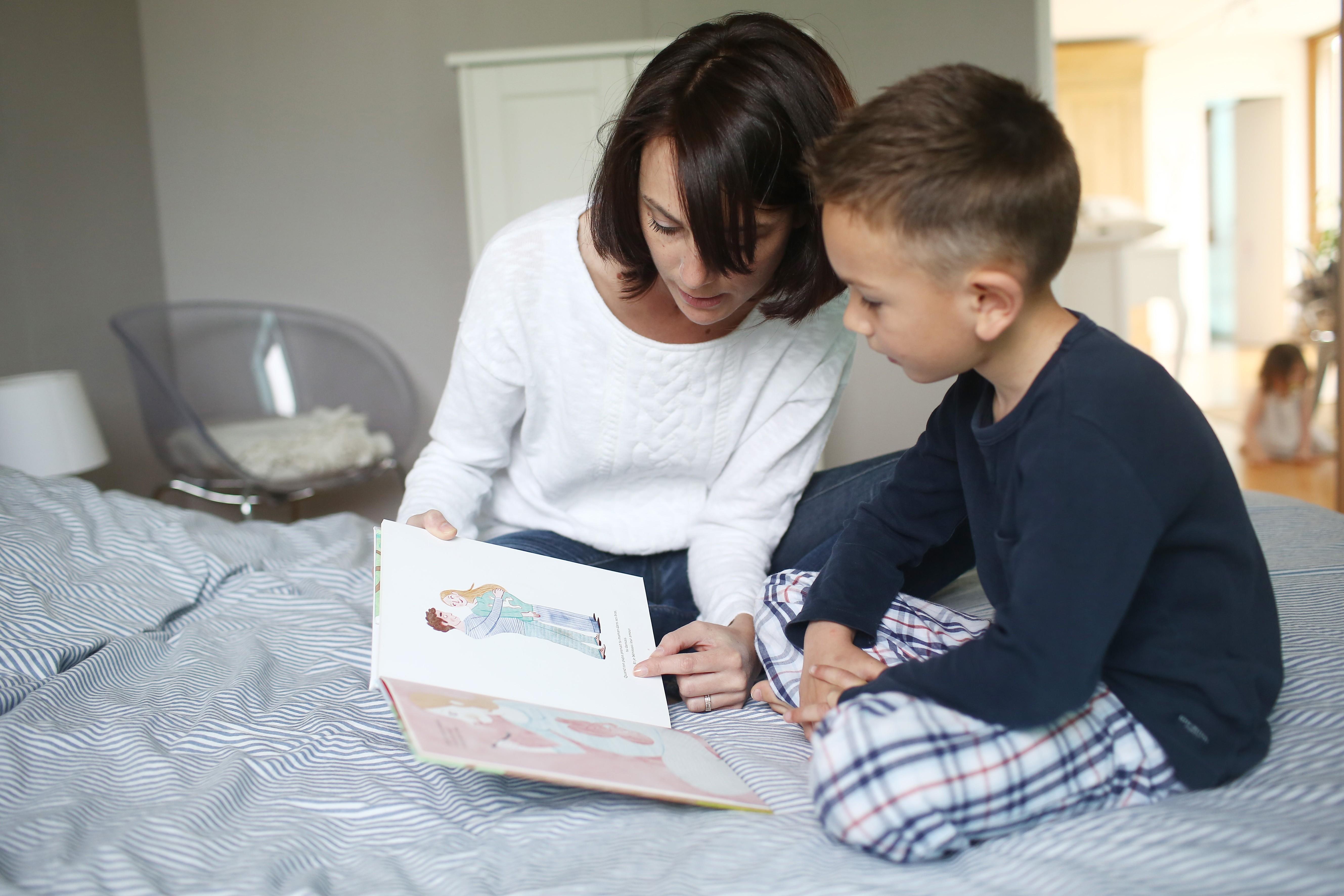 Mãe lendo um livro para seu filho de 5 anos de idade. Eles estão sentados em cima de uma cama.