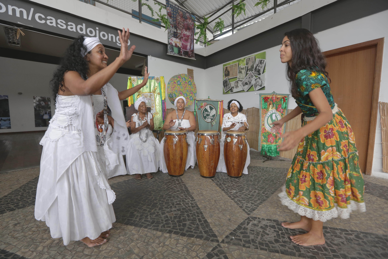 Mulher toda de branco gesticula para Bela Gil (que está de saia longa, rodada e florida) e a ensina a dançar jongo. Ao fundo, mulheres jongueiras batucam instrumento musical.