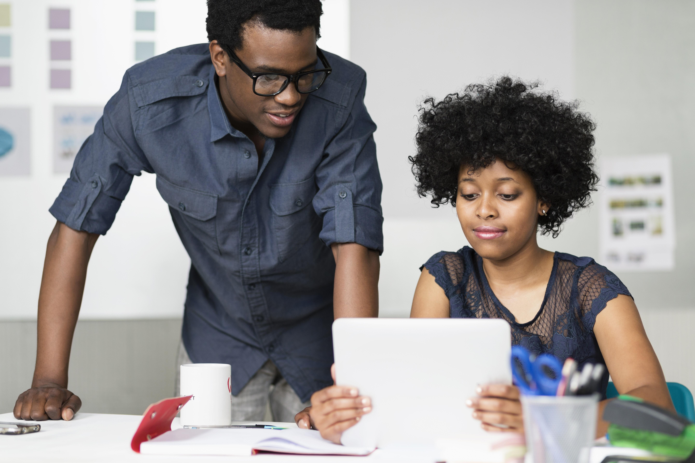 Dois colegas, um homem negro de pé e uma mulher negra sentada em frente a uma mesa, trabalham com um tablet.