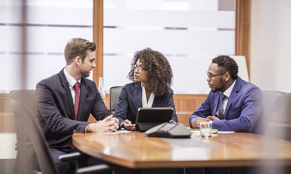 Três colegas de trabalho reunidos ao redor de uma mesa em uma sala de reunião: um homem branco, uma mulher negra e outro homem negro.
