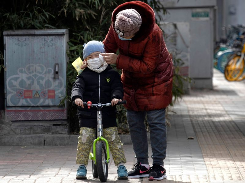 Reprodução G1: Mulher limpa o rosto de uma criança com um lenço nas ruas de Pequim, na China, nesta quinta-feira (12) — Foto: Han Han Guan/AP