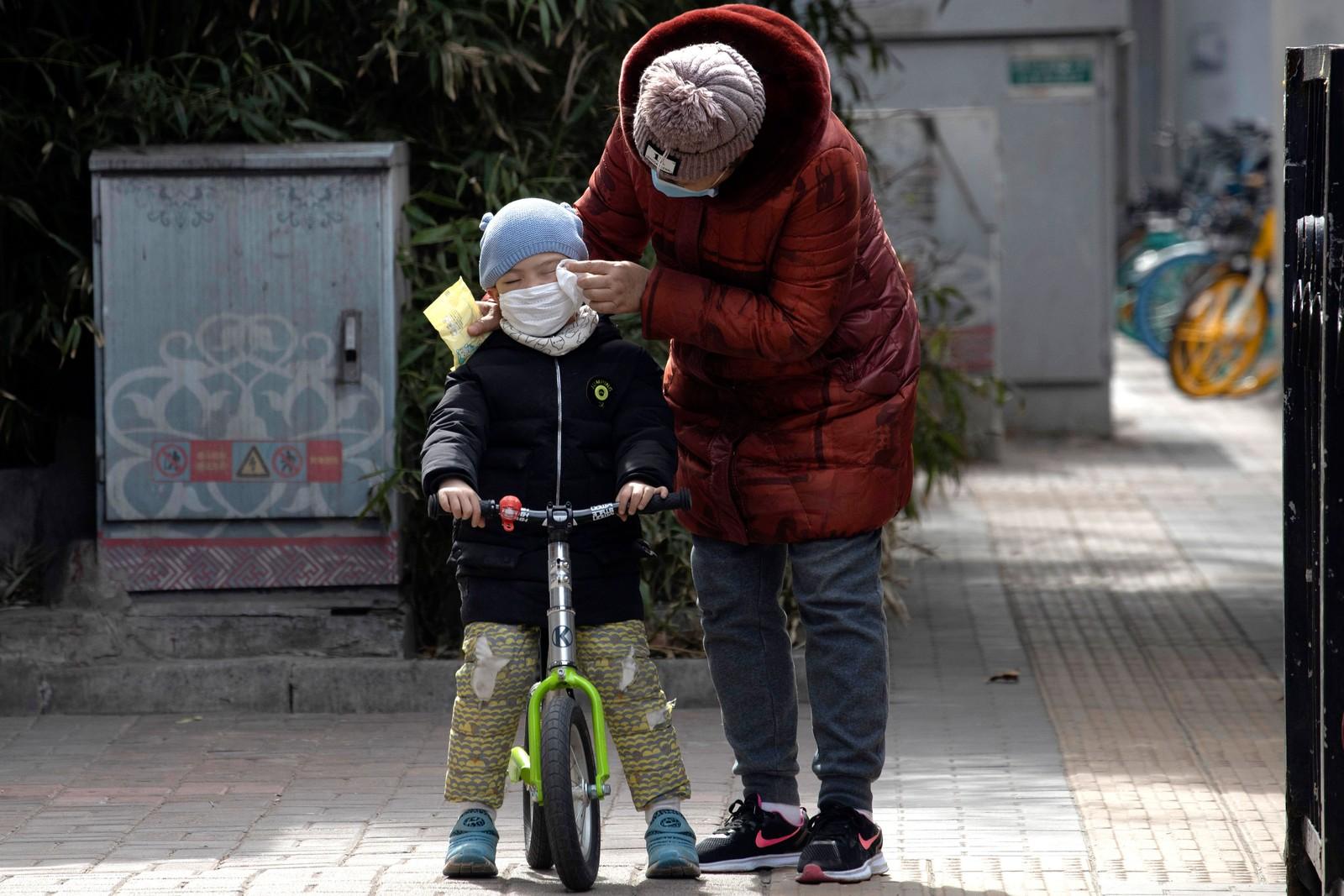Mulher limpa o rosto de uma criança com um lenço nas ruas de Pequim, na China
