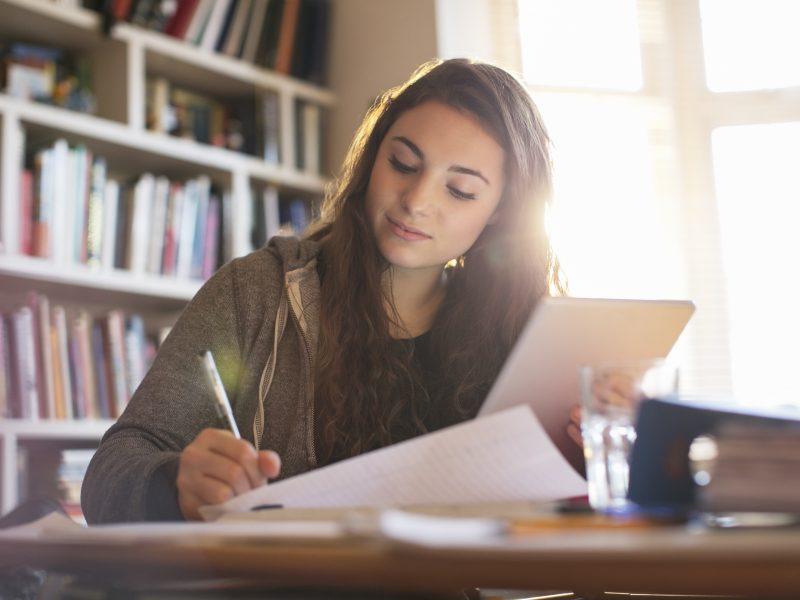 Menina adolescente com seu tablet faz a lição de casa em uma mesa.
