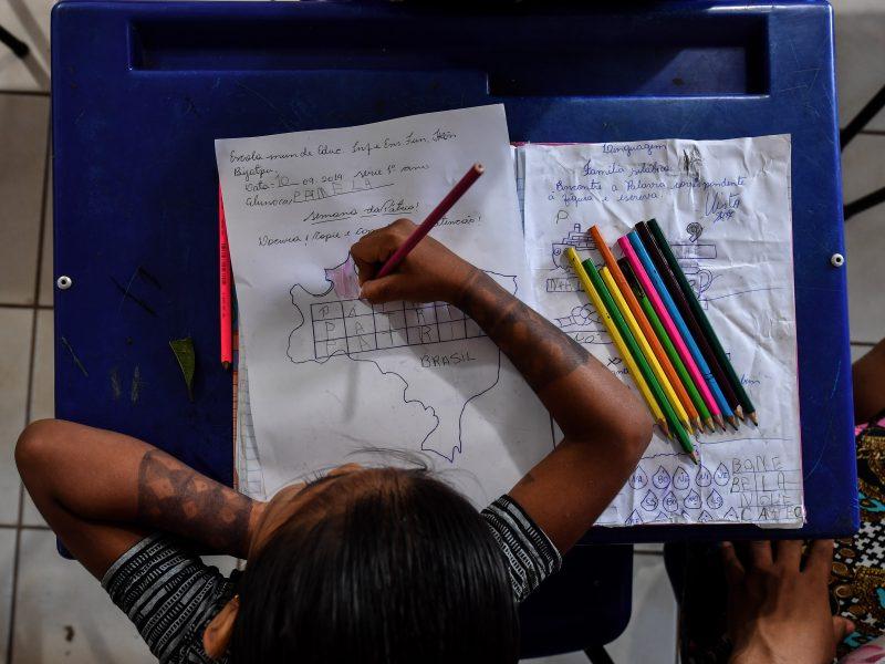 Criança indígena Munduruku faz dever de casa com atenção na escola localizada na reserva indígena em Itaituba, no Pará.