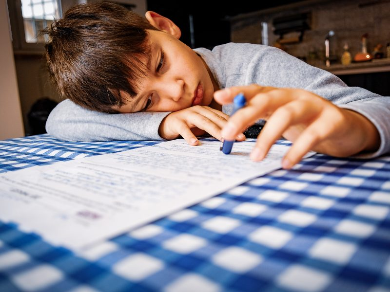 Uma criança faz seu dever de casa na mesa da cozinha. A escola teve que se adaptar a dar aulas à distância desde que começou o confinamento.